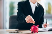 partial view of businesswoman putting coin into pink piggy bank