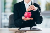 cropped shot of businesswoman putting coin into pink piggy bank