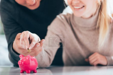 cropped shot of happy couple putting coin into pink piggy bank