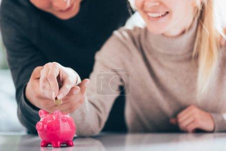 Schnappschuss von glücklichem Paar, das Münze in rosa Sparschwein steckt