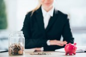 close-up view of pink piggy bank and glass jar with coins, smiling businesswoman behind
