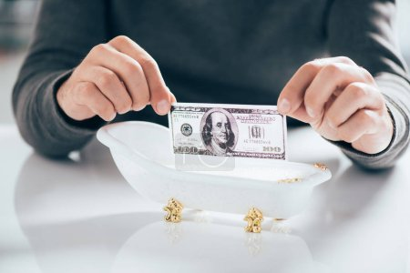 Photo for Cropped shot of man holding dollar banknote above tub, money laundering concept - Royalty Free Image