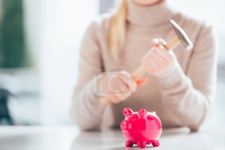 close-up view of pink piggy bank and woman holding hammer behind