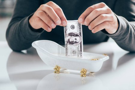 cropped shot of man washing dollar banknote in small bathtub, money laundering concept