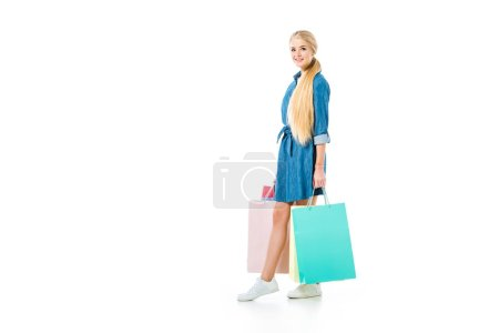 Beautiful blonde girl with shopping bags isolated on white