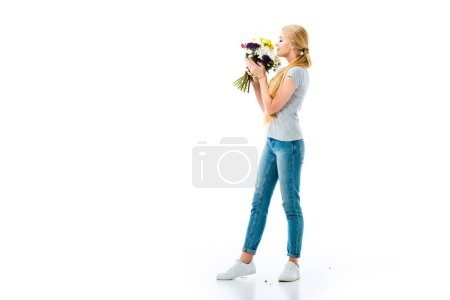 beautiful blonde girl smelling flowers and looking at them isolated on white