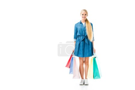 Happy girl in denim dress with shopping bags after successful shopping isolated on white