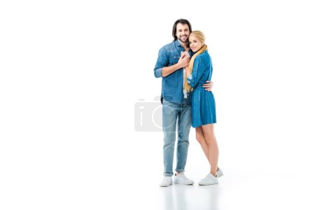 Girl in denim dress and man in jeans and denim shirt hugging each other  isolated on white