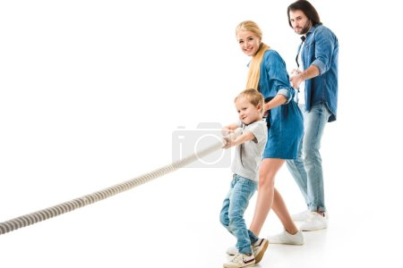 Parents and their little son in denim clothes pulling rope isolated on white