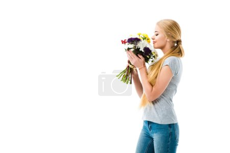 Beautiful girl smelling bouquet of flowers isolated on white