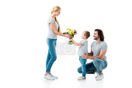 Photo for Son presenting bouquet of flowers his mother isolated on white - Royalty Free Image