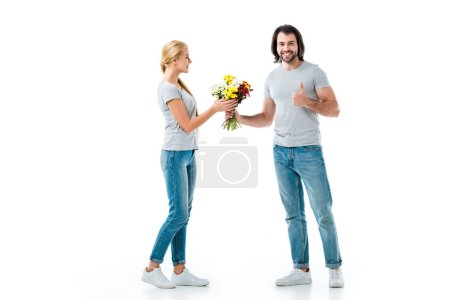 handsome man presenting flowers and showing thumb up isolated on white