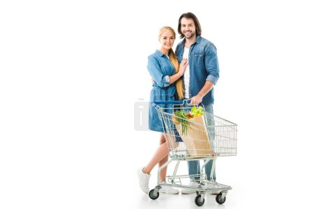 Happy couple with trolley hugging and smiling isolated on white