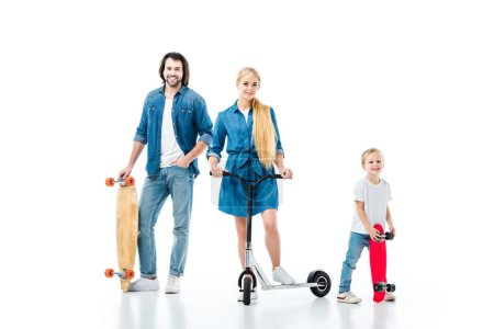 Happy family having fun with scooter and skateboards isolated on white