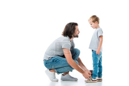 Photo for Caring father helping his son to tie shoelace isolated on white - Royalty Free Image