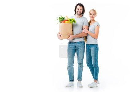Photo pour Beau couple avec des sacs d'épicerie en regardant caméra isolé sur blanc - image libre de droit