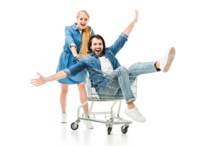 Photo for Excited couple laughing and having fun with shopping cart isolated on white - Royalty Free Image