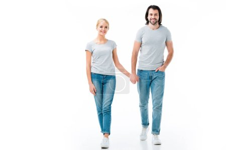 Lovely couple in grey t-shirts holding hands and smiling at camera isolated on white