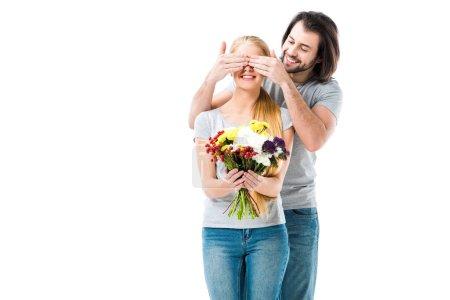 Photo pour Awesome femme tenant des fleurs tout en fermant les yeux de l'homme pour faire une surprise, isolée sur blanc - image libre de droit