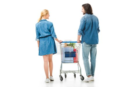 Photo for Back view of couple holding shopping cart with bags isolated on white - Royalty Free Image