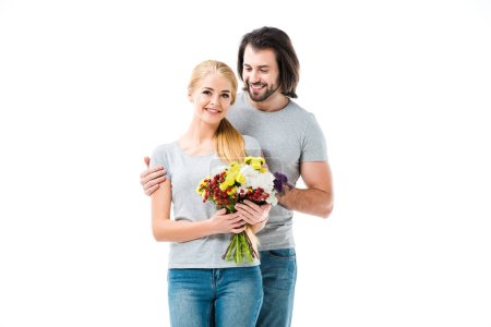 Wonderful couple hugging while woman holding flowers isolated on white