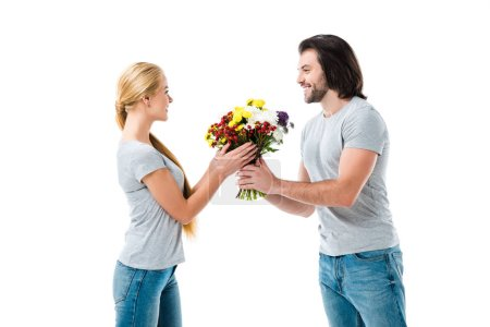 Lovely couple looking at each other and holding beautiful flowers isolated on white