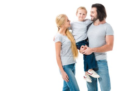 Lovely parents holding their son and looking at each other isolated on white