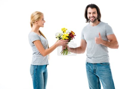 Beautiful couple, man holding flowers and pointing thumb up isolated on white