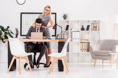 businesswoman making massage to colleague at workplace in office, office romance concept