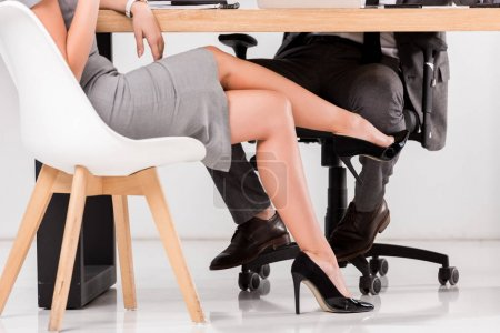 cropped shot of businesswoman flirting with businessman at workplace in office