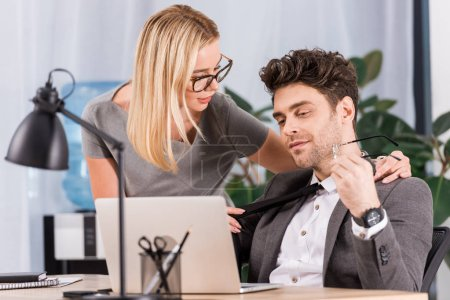 portrait of businesswoman pulling colleagues tie at workplace with laptop in office, flirt and office romance concept