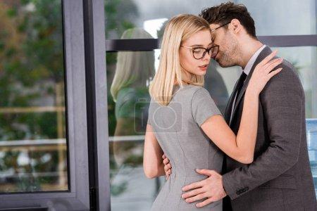 Photo pour Vue de côté de gens d'affaires hugging en bureau, concept de romance de flirt et de bureau - image libre de droit