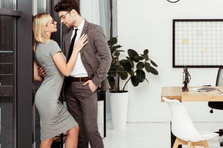 Photo pour Vue de côté de collègues de travail jeune flirt au bureau - image libre de droit