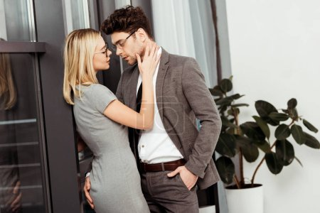 side view of businesspeople hugging looking at each other in office, flirt and office romance concept
