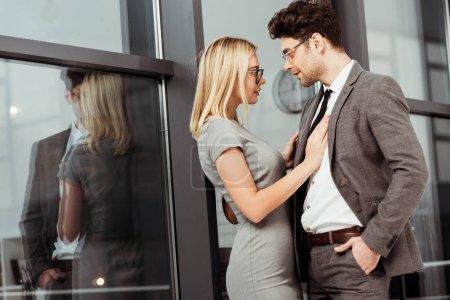 Photo pour Vue de gens d'affaires étreindre et regardant les uns les autres dans le bureau, flirter et office romance concept - image libre de droit