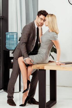 side view of young business colleagues flirting at workplace in office, offirce romance concept