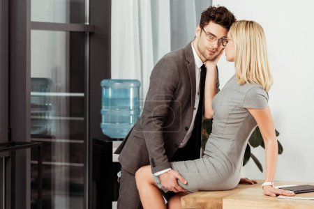 side view of business colleagues flirting at workplace in office, offirce romance concept