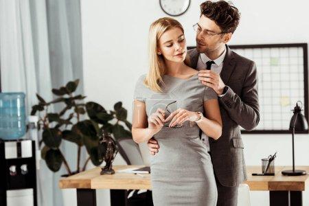 Photo pour Jeunes avocats flirter au cours de la journée de travail au bureau, bureau romance concept - image libre de droit
