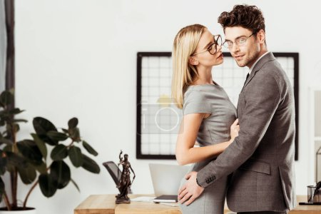 young lawyers hugging each other while standing in office, flirt and office romance concept