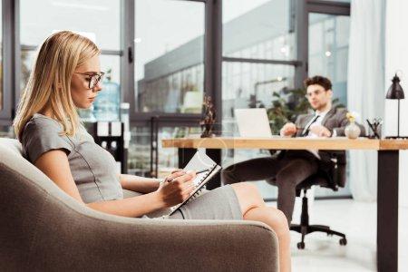 Photo pour Femme d'affaires, prendre des notes dans l'ordinateur portable assis dans le fauteuil avec collègue sur lieu de travail au bureau - image libre de droit