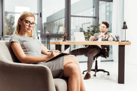 businesswoman with notebook looking at camera while sitting in armchair with colleague at workplace in office