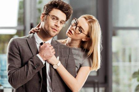 portrait of beautiful businesswoman hugging stylish businessman in office, flirt and office romance concept