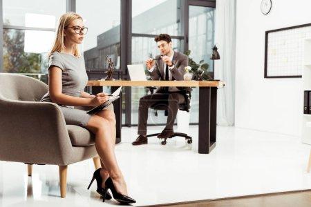 Photo pour Jeune femme d'affaires avec ordinateur portable assis dans le fauteuil avec collègue sur lieu de travail au bureau - image libre de droit