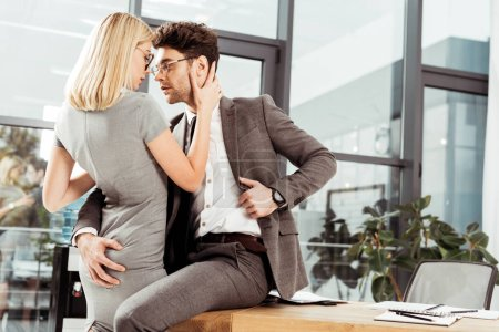 business colleagues hugging and flirting at workplace, office romance concept
