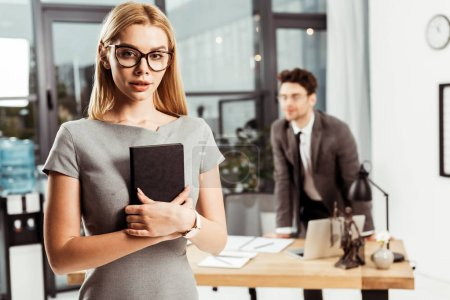 selective focus of young female lawyer with notebook looking at camera while colleague standing at workplace in office