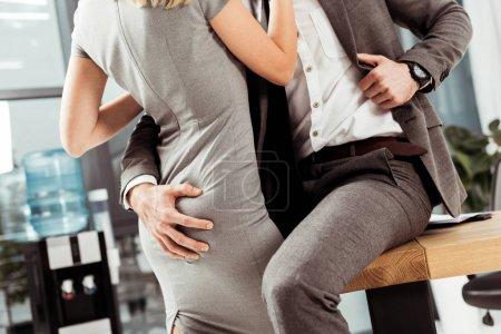 Photo pour Plan recadré de collègues d'affaires étreignant et flirtant sur le lieu de travail, concept de romance de bureau - image libre de droit