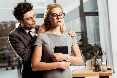 portrait of male lawyer flirting with colleague in office, office romance concept