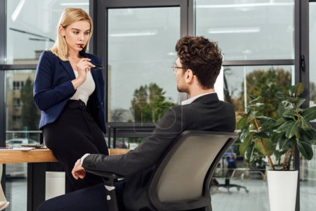 attractive businesswoman flirting with business colleague at workplace in office