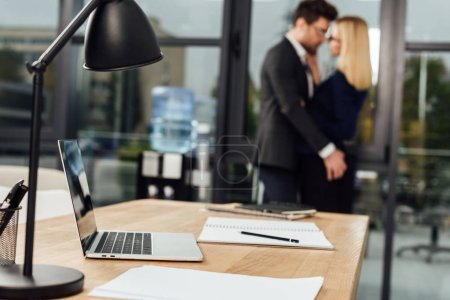 Photo pour Mise au point sélective du milieu de travail avec ordinateur portable et les gens d'affaires hugging derrière en bureau, bureau romance concept - image libre de droit