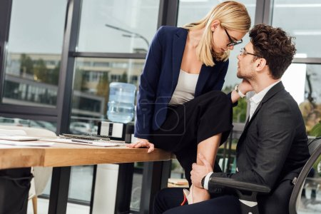 attractive young businesswoman flirting with business colleague at workplace in office